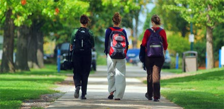 Three students walking outside.